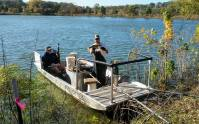 Biologists show off Largemouth Bass and electrofishing boat